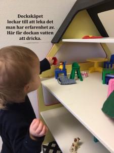 Lek efter erfarenheter i dockskåpet. Dockbarnet får vatten, mamman och pappan pussas sen vill alla sitta i soffan.